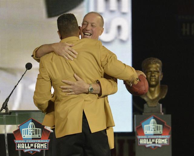 Former Buffalo Bills quarterback Jim Kelly, back, hugs inductee Andre Reed during the Pro Football Hall of Fame enshrinement ceremony Saturday, Aug. 2, 2014, in Canton, Ohio. (AP Photo/David Richard)