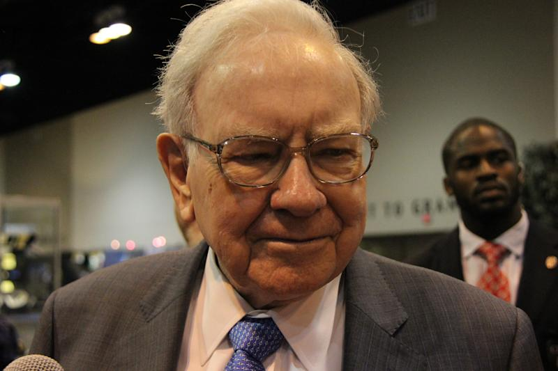 Warren Buffett, with a person in the background.