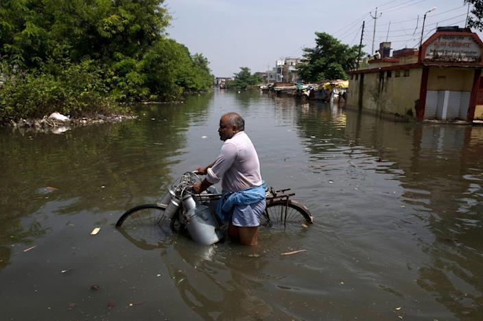<p>An Indian milkman wades through flooded water with his bicycle in Varanasi, India, Friday, Aug. 26, 2016. (AP Photo/Tsering Topgyal)</p>