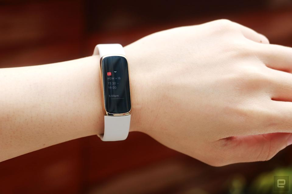 <p>Full frontal view of the Fitbit Luxe with a light pink silicone band on a wrist against a dark brown background. The screen shows a calendar notification for an event from 5:30pm to 7pm.</p>