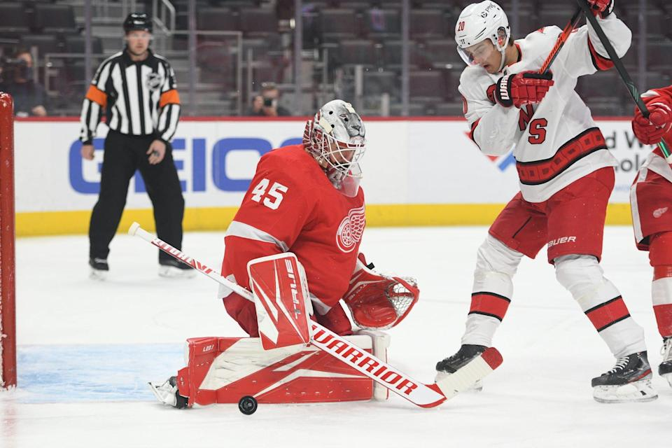 Detroit Red Wings goaltender Jonathan Bernier (45) makes a save in front of Carolina Hurricanes center Sebastian Aho (20) during the first period March 14, 2021, at Little Caesars Arena in Detroit.