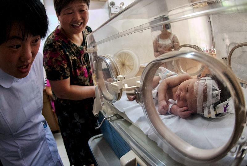 In this Tuesday, May 28, 2013 photo, a Chinese woman and a nurse look at the baby who was rescued after being trapped in a sewage pipe moments after his birth, as he sleeps in an incubator at a hospital in Pujiang county in east China's Zhejiang province. The newborn has been released from the hospital into the care of his grandparents. Local officials and media reports said Thursday, May 30, 20123, that authorities have concluded it was an accident, meaning his unwed mother is unlikely to be criminally charged. (AP Photo) CHINA OUT