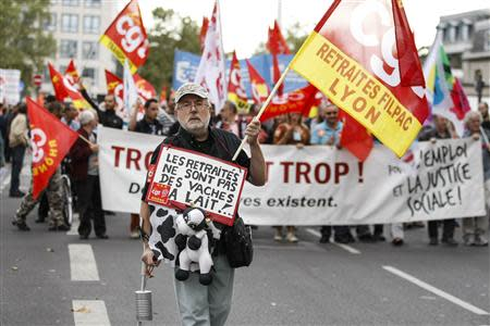 A man holds a CGT labour union flag during a demonstration over pension reforms in Lyon, September 10, 2013. REUTERS/Emmanuel Foudrot