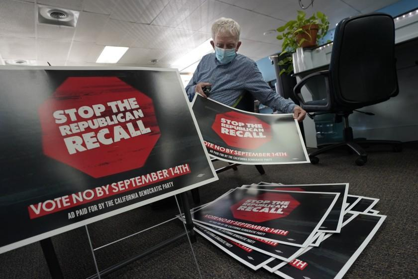 FILE - In this July 29, 2021, file photo, volunteer Merle Canfield assembles yard signs against the Sept. 14, recall election of Gov. Gavin Newsom, at the Fresno County Democratic Party headquarters in Fresno, Calif. Democratic state lawmakers Sen. Steve Glazer and Assemblyman Marc Berman called for reforming the recall election requirements, Wednesday Sept. 15, 2021. This could include increasing the number of signatures to force a recall election, raising the standards to require malfeasance on the part of the office-holder and change the current process in which someone with a small percentage of votes could replace a sitting governor. (AP Photo/Rich Pedroncelli, File)
