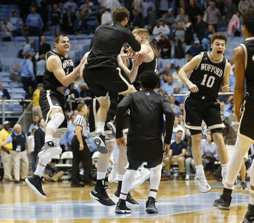 "Wofford players including <a class=""link rapid-noclick-resp"" href=""/ncaab/players/132401/"" data-ylk=""slk:Fletcher Magee"">Fletcher Magee</a>, far left, and Nathan Hoover (10) celebrate after beating North Carolina 79-75 an NCAA college basketball game in Chapel Hill, N.C., Wednesday, Dec. 20, 2017. (AP Photo/Ellen Ozier)"