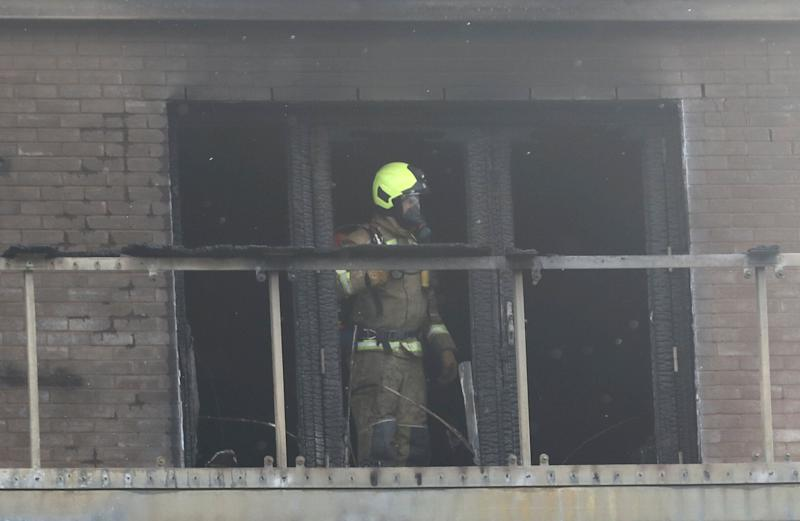 Firefighter attends to a building after a fire broke out in Barking, London, Britain, June 9, 2019. REUTERS/Simon Dawson