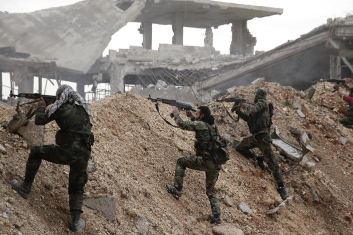 FILE - In this Dec. 5, 2016 file photo, Syrian army soldiers fire their weapons during a battle with rebel fighters at the Ramouseh front line, east of Aleppo, Syria. Syrians are marking 10 years since peaceful protests against President Bashar Assad's government erupted in March 2011, touching off a popular uprising that quickly turned into a full-blown civil war. (AP Photo/Hassan Ammar, File)