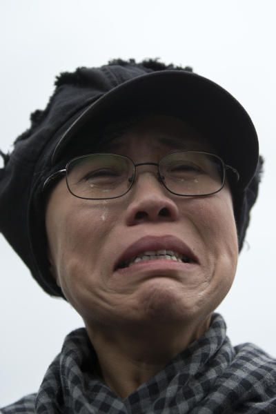 Liu Xia, wife of imprisoned Nobel Peace Prize winner Liu Xiaobo, cries outside Huairou Detention Center where her brother Liu Hui has been jailed in Huairou district, on the outskirts of Beijing, China, Sunday, June 9, 2013. A court sentenced, Liu Hui, the brother-in-law of China's imprisoned Nobel Peace Prize winner Liu Xiaobo to 11 years in prison Sunday — an unusually harsh punishment for a business dispute that the activist's wife immediately decried as a warning to the whole family. (AP Photo/Alexander F. Yuan)