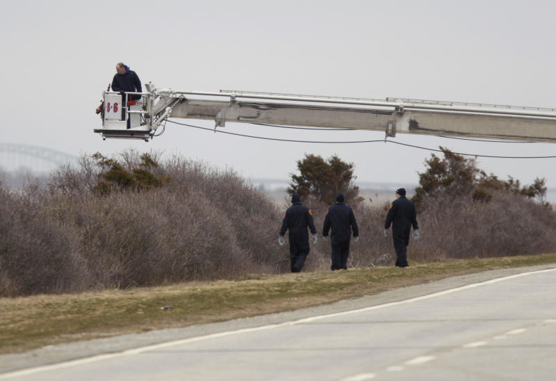 Emergency personnel search in the brush with the help of a ladder on a fire truck near Oak Beach, N.Y., Monday, April 4, 2011.  (AP Photo/Seth Wenig)