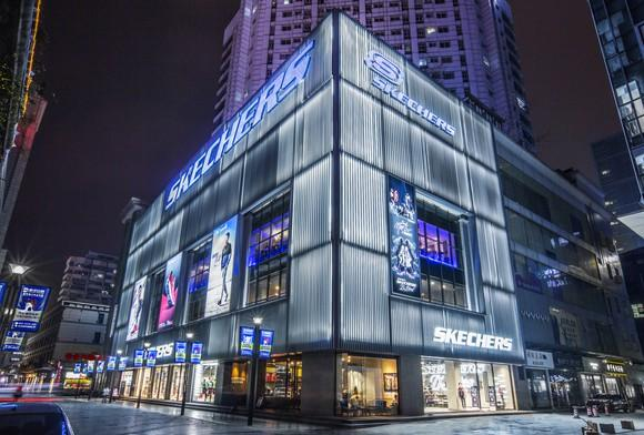 A new Skechers store in China amid high-rise buildings. The store is about four stories, has gray metal sides, and big windows displaying Skechers products.