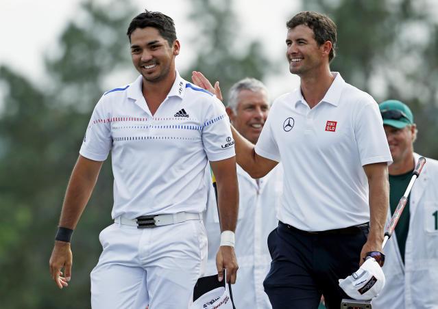 Defending Masters champion Adam Scott, right, of Australia, pats Jason Day, of Australia, on the back on the 18th green following his fourth round of the Masters golf tournament Sunday, April 13, 2014, in Augusta, Ga. (AP Photo/Matt Slocum)