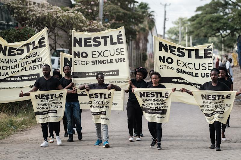 Activisits of the environmental group Greenpeace Africa walks with banners as they protest against Swiss food giant Nestle for their single-use plastic packages, on April 16, 2019 at the entrance of Nestle's factory in Nairobi. - According to Greenpeace Africa, last year, Nestle produced a 1.7 million tonnes of plastic packaging, nearly 300 garbage trucks worth a day. By their brand audits, Nestle was one of the top three plastic polluters in the world. (Photo by Yasuyoshi CHIBA / AFP) (Photo credit should read YASUYOSHI CHIBA/AFP/Getty Images)
