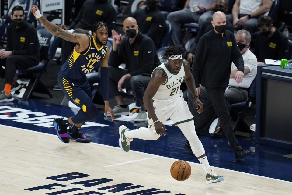 Milwaukee Bucks' Jrue Holiday (21) dribbles past Indiana Pacers' Oshae Brissett (12) during the second half of an NBA basketball game Thursday, May 13, 2021, in Indianapolis. (AP Photo/Darron Cummings)