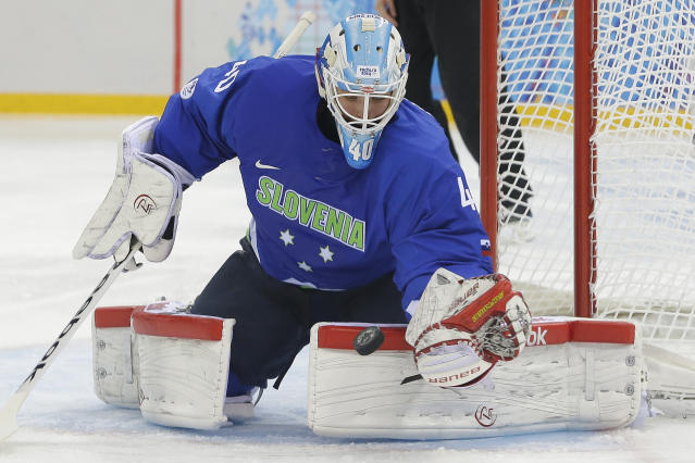 Slovenia goaltender Luka Gracnar stops a shot on the goal during the 2014 Winter Olympics men's ice hockey game against USA at Shayba Arena Sunday, Feb. 16, 2014, in Sochi, Russia. (AP Photo/Matt Slocum)