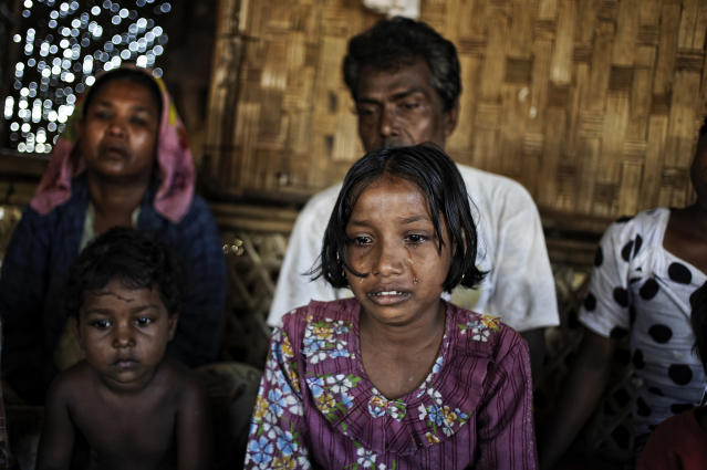 In this Nov. 29, 2013 photo, Tawhera Begum, center, sister of Senwara, cries as she watches a video interview of her sister at the Ohn Taw refugee camp on the outskirts of Sittwe, Myanmar. After their tiny Muslim village in Myanmar's northwest Rakhine had been destroyed in a fire set by an angry Buddhist mob, Senwara, 9, and brother, Mohamed, 15, became separated from the family. (AP Photo/Kaung Htet)