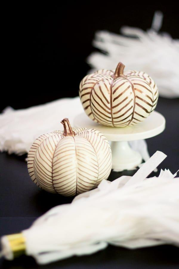 """<p>These chic pumpkins require only one material: paint pens. If you're using orange pumpkins instead of white, paint them a solid color before decorating with patterns.</p><p><em><strong>Get the tutorial from <a href=""""https://lovelyindeed.com/diy-carve-copper-herringbone-pumpkins/"""" rel=""""nofollow noopener"""" target=""""_blank"""" data-ylk=""""slk:Lovely Indeed"""" class=""""link rapid-noclick-resp"""">Lovely Indeed</a>.</strong></em> </p>"""