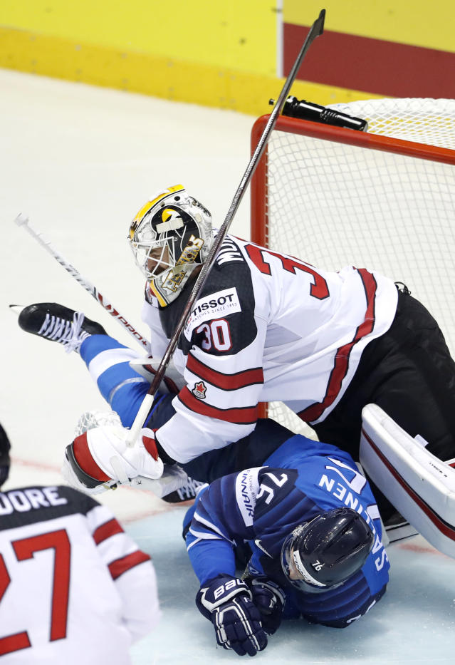 Finland's Jere Sallinen, down, collides with Canada's goaltender Matt Murray, up, during the Ice Hockey World Championships group A match between Finland and Canada at the Steel Arena in Kosice, Slovakia, Friday, May 10, 2019. (AP Photo/Petr David Josek)
