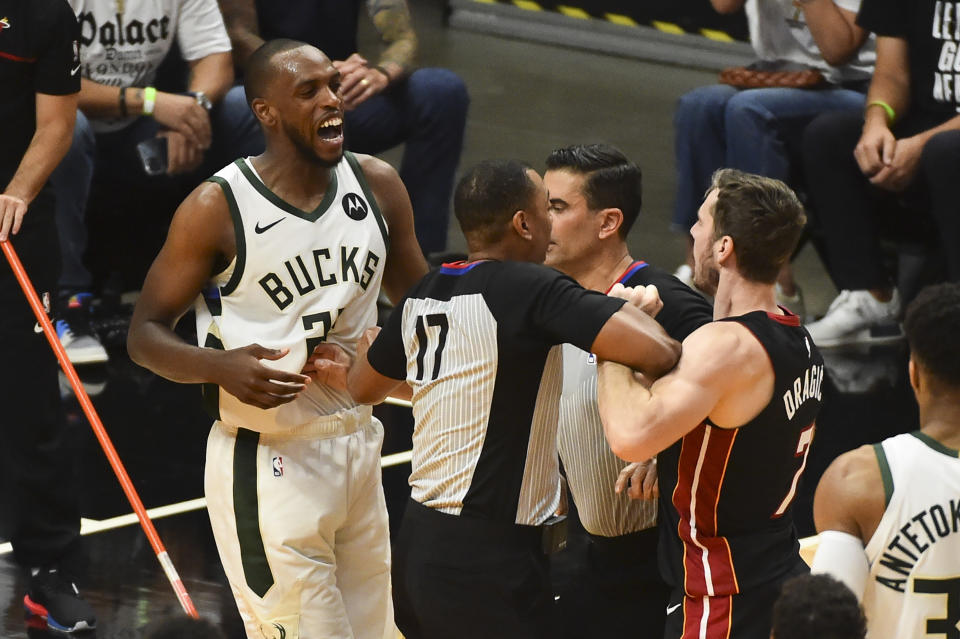 MIAMI, FL - MAY 29: Khris Middleton #22 of the Milwaukee Bucks is seperated from Goran Dragic #7 of the Miami Heat by referee Karl Lane #77 during Game Four of the Eastern Conference first-round playoff series at American Airlines Arena on May 29, 2021 in Miami, Florida. (NOTE TO USER: User expressly acknowledges and agrees that, by downloading and or using this photograph,  User is consenting to the terms and conditions of the Getty Images License Agreement.(Photo by Eric Espada/Getty Images)