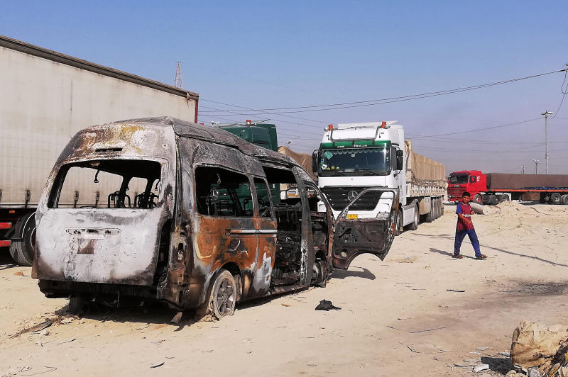 A destroyed minibus sits near an Iraqi army checkpoint about 10 kms. (6 miles) south of Karbala, Iraq, Saturday, Sept. 21, 2019. A bomb exploded on a minibus packed with passengers outside the Shiite holy city of Karbala Friday night, killing and wounding civilians, Iraqi security officials said. (AP Photo/Hadi Mizban)