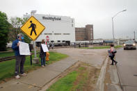 FILE - In this May 20, 2020, file photo, residents cheer and hold thank-you signs to greet employees of a Smithfield pork processing plant as they begin their shift in Sioux Falls, S.D. Workers on farms and at meatpacking plants who were severely affected by the coronavirus pandemic will be eligible to get grants of up to $600 per person as part of a new $700 million aid program the U.S. Department of Agriculture announced Tuesday, Sept. 7, 2021. (AP Photo/Stephen Groves, File)
