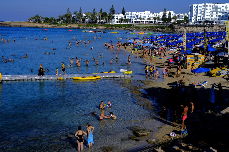 Swimmers cool off from the mid-summer heat in the clear east Mediterranean waters of Cyprus' Fig Tree Bay in the coastal resort of Protaras near Ayia Napa on Saturday, July 18 2020. Tourism-reliant Cyprus projects that this year, it will receive less than a quarter of the record 3.9 million holiday makers it got in 2019 because of the global coronavirus pandemic. (AP Photo/Petros Karadjias)