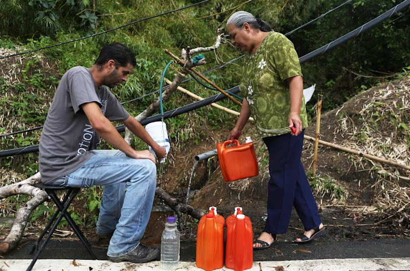 Migdalia Aceuedo and her son collect spring water in Utuado near a downed power line. Their house and much of the town is without running water or power.