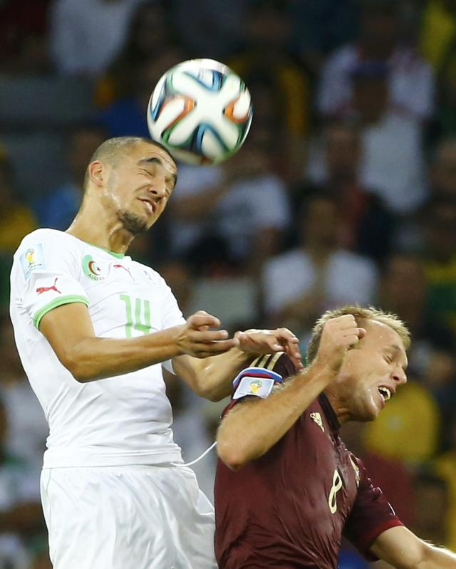 Algeria's Nabil Bentaleb jumps for the ball with Russia's Denis Glushakov (R) during their 2014 World Cup Group H soccer match at the Baixada arena in Curitiba June 26, 2014. REUTERS/Murad Sezer (BRAZIL - Tags: SOCCER SPORT WORLD CUP)