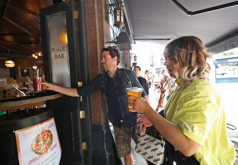 Customers are served takeaway drinks from the Cat & Mutton pub in Broadway Market, London, as further restrictions are lifted to bring England out of the coronavirus lockdown. (Photo by Yui Mok/PA Images via Getty Images)