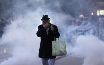 A man puts his hand over his mouth to protect it from smoke during a protest against vaccinations and coronavirus measures in Ljubljana, Slovenia, Tuesday, Oct. 5, 2021. EU leaders are meeting Tuesday evening in nearby Kranj, Slovenia, to discuss increasingly tense relations with China and the security implications of the chaotic U.S.-led exit from Afghanistan, before taking part in a summit with Balkans leaders on Wednesday. (AP Photo/Petr David Josek)