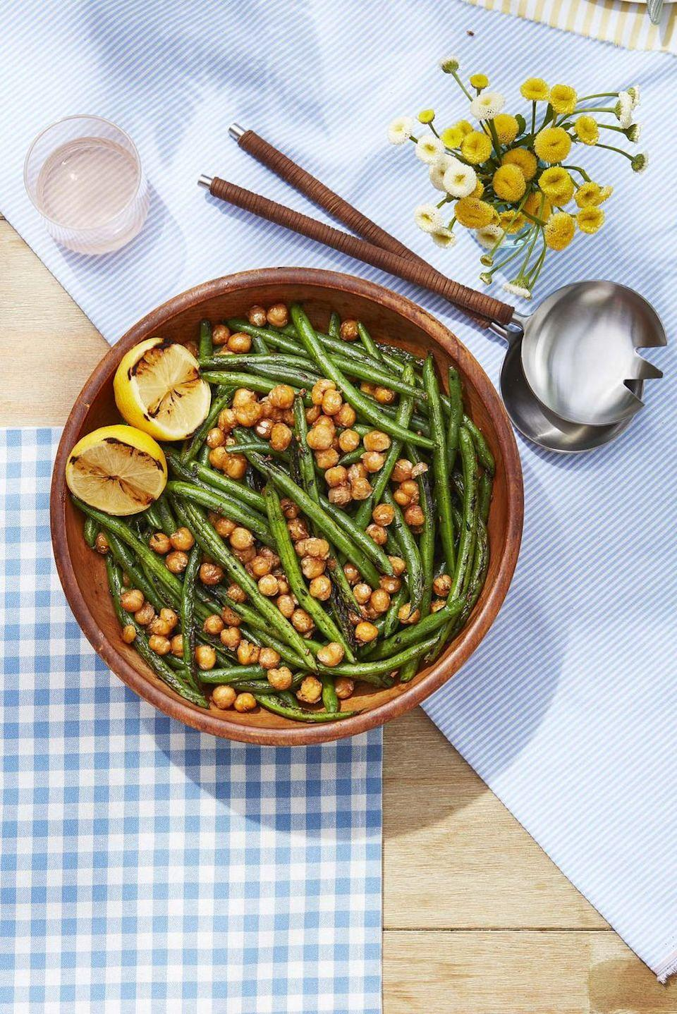 """<p>Whether they're cooked over an open fire or on your kitchen stove, these crispy green beans and chickpeas have just a hint of cumin and will have guests fighting over seconds.</p><p><strong><a href=""""https://www.countryliving.com/food-drinks/a32353817/green-beans-with-crispy-chickpeas/"""" rel=""""nofollow noopener"""" target=""""_blank"""" data-ylk=""""slk:Get the recipe"""" class=""""link rapid-noclick-resp"""">Get the recipe</a>.</strong> </p>"""