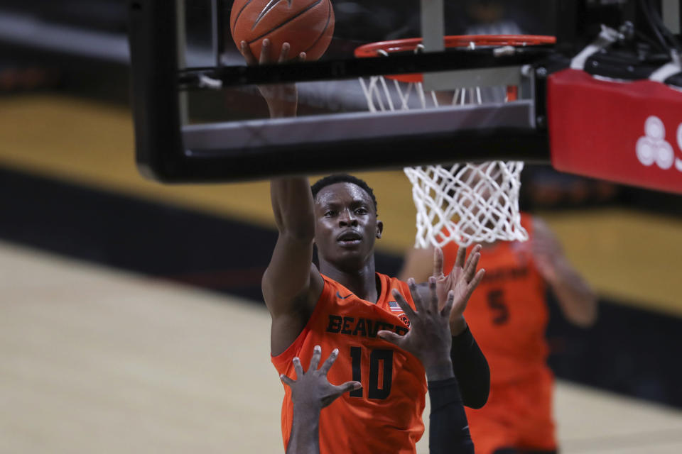 Oregon State's Warith Alatishe (10) shoots over Oregon's Amauri Hardy during the second half of an NCAA college basketball game in Corvallis, Ore., Sunday, March 7, 2021. (AP Photo/Amanda Loman)