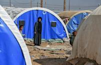 A woman and child are seen outside tents in Al-Jadaa camp on the outskirts of Qayyarah, south of the Iraqi city of Mosul, in this file picture taken on February 11, 2021