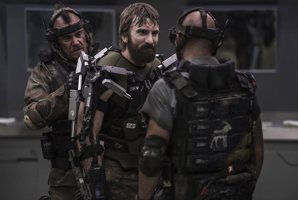 Drake (Brandon Auret, left) and Crowe (Josh Blacker, right) help Kruger (Sharlto Copley) don a new EXO suit in TriStar Pictures' ELYSIUM.