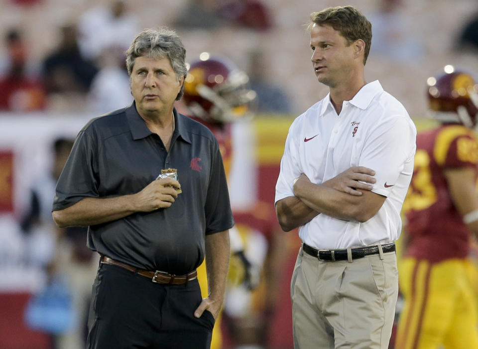 Then-Southern California coach Lane Kiffin (R) and then-Washington State coach Mike Leach watch their teams warm up for an NCAA college football game in Los Angeles, Saturday, Sept. 7, 2013. (AP Photo/Chris Carlson)