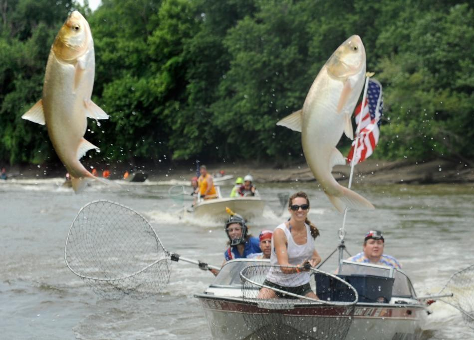 Participants try to snag Asian carp during the Redneck Fishing Tournament in Bath, Ill.