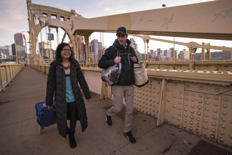 This image released by 412 Food Rescue shows Melinda Angeles and Eli Thomas transporting a donation of bagels from Bruegger's Bagels across the 9th Street bridge to a North Side senior center in Pittsburgh. While millions of people struggle with food insecurity and hunger nationwide, the USDA estimates that more than 30% of the food in America is wasted each year.  (Nancy Andrews/412 Food Rescue via AP)