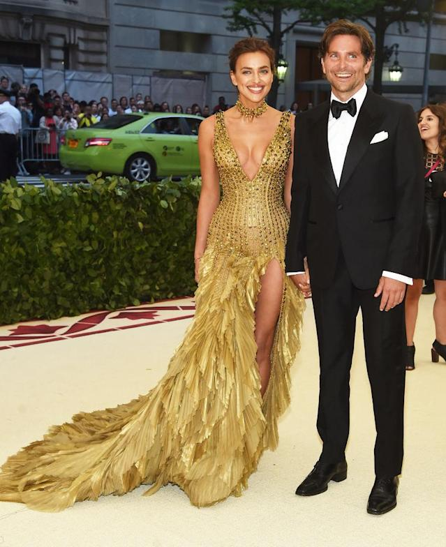<p>The model outshined her husband in a gold Versace gown with feathers. (Photo: Getty Images) </p>