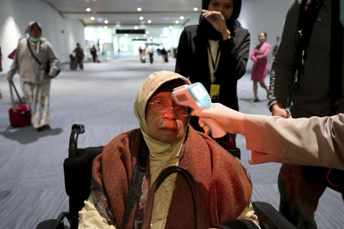 A health official scans the body temperature of a passenger as she arrives at the Soekarno-Hatta International Airport in Tangerang, Indonesia. (AP Photo/Tatan Syuflana)