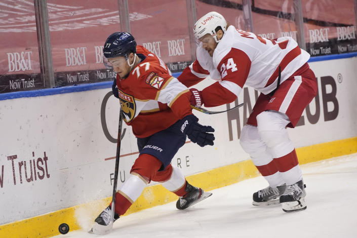 Florida Panthers center Frank Vatrano (77) and Detroit Red Wings defenseman Jon Merrill (24) battle for the puck during the second period of an NHL hockey game, Sunday, Feb. 7, 2021, in Sunrise, Fla. (AP Photo/Wilfredo Lee)