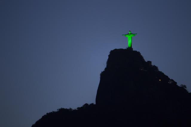 The Christ the Redeemer statue is illuminated in green in commemoration of St. Patrick's Day in Rio de Janeiro, Brazil, Monday, March 17, 2014. (AP Photo/Felipe Dana)