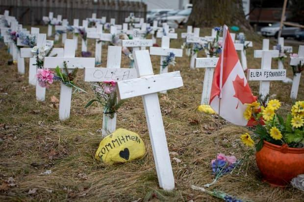 Crosses representing residents who died of COVID-19 cover the lawn of Camilla Care Community in Mississauga, Ont., on Jan. 13, 2021.