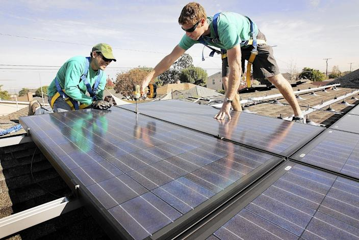 """Some climate advocates would rather see policymakers focus on smaller, more local forms of clean power, such as rooftop solar. Above, SolarCity workers Joey Ramirez, left, and Taran Stone install solar modules on the roof of a Long Beach home. <span class=""""copyright"""">(Al Seib / Los Angeles Times)</span>"""