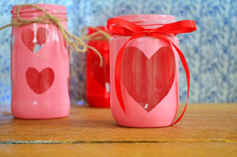 """<p>A <a href=""""https://www.countryliving.com/diy-crafts/how-to/g2963/diy-valentines-day-cards/"""" rel=""""nofollow noopener"""" target=""""_blank"""" data-ylk=""""slk:DIY Valentine's Day card"""" class=""""link rapid-noclick-resp"""">DIY Valentine's Day card</a> or gift is an easy, thoughtful way to remind your partner or loved ones how much you care and that you are thinking of them on Saint Valentine's Day. That's why these DIY Valentine's Day mason jar ideas are a simple, personal way to brighten up anyone's February 14. Many of these sweet ideas won't take much time to put together. There are tutorials that include cute print-outs with clever <a href=""""https://www.countryliving.com/life/a30446128/valentines-day-puns/"""" rel=""""nofollow noopener"""" target=""""_blank"""" data-ylk=""""slk:Valentine's Day puns"""" class=""""link rapid-noclick-resp"""">Valentine's Day puns</a>, such as the candy-filled """"S'More Love for You"""" or """"Love You to Pieces"""" jars. There are also Mason jars that double as love-inspired decorations, such as the glitter votives that sparkle in the candlelight or the thumbprint heart jar that could be displayed all year. You could also make these as a DIY add-on to your <a href=""""https://www.countryliving.com/shopping/gifts/g1416/valentines-day-gifts/"""" rel=""""nofollow noopener"""" target=""""_blank"""" data-ylk=""""slk:Valentine's Day gifts"""" class=""""link rapid-noclick-resp"""">Valentine's Day gifts</a>, or perhaps even as a gift holder if you got the recipient something small or gift them a bouquet of flowers. For anyone who's hoping to flex their creative muscles this February, there are tons of <a href=""""https://www.countryliving.com/diy-crafts/g1093/valentine-day-crafts/"""" rel=""""nofollow noopener"""" target=""""_blank"""" data-ylk=""""slk:Valentine's Day crafts"""" class=""""link rapid-noclick-resp"""">Valentine's Day crafts</a> that will make great gifts for anyone. These creative Valentine's Day mason jar ideas are a reliable option for anyone looking for a personal touch without having to spend tons of time on it or money showing your """