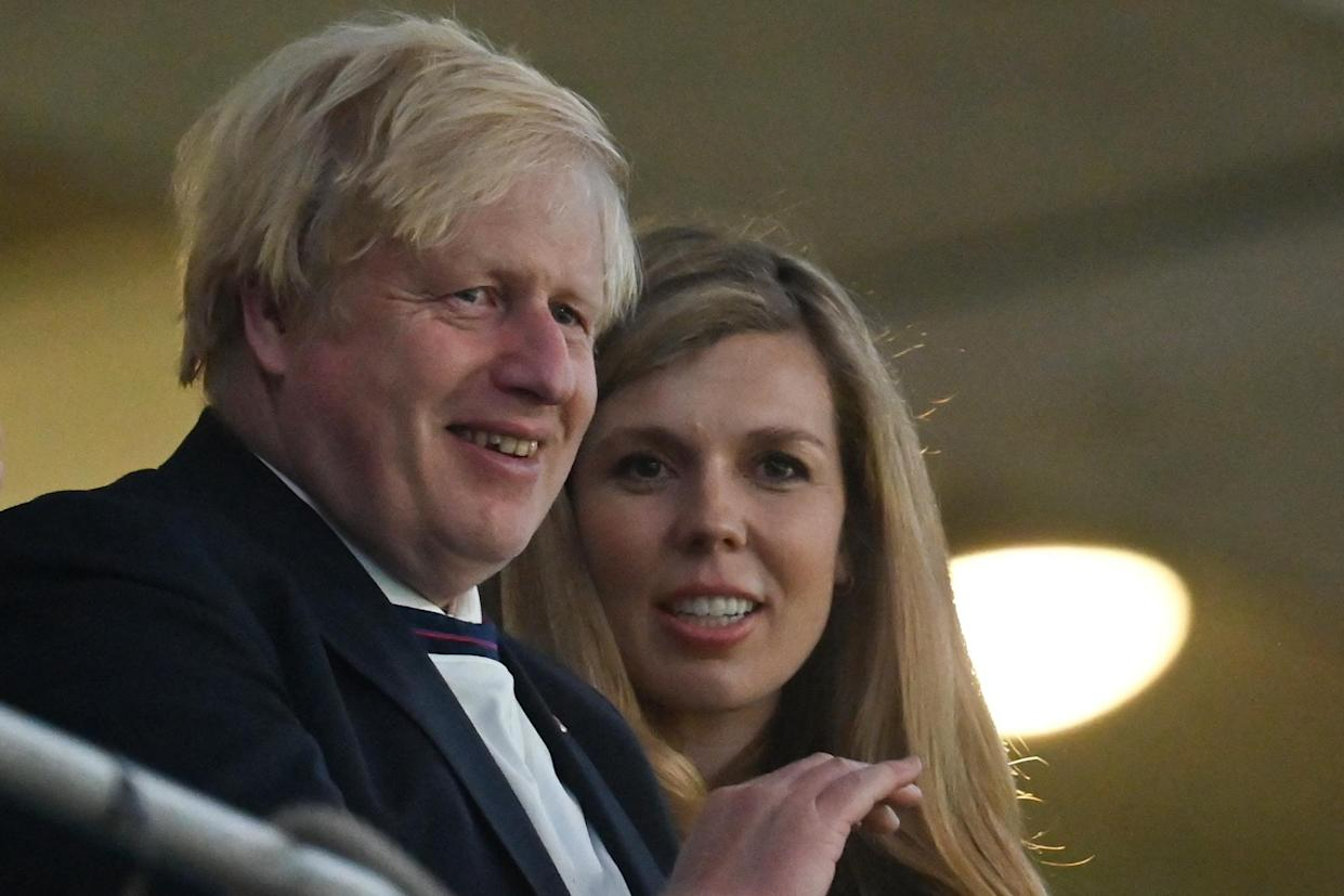 UK Prime Minister Boris Johnson (L) and his spouse Carrie (R) celebrate the win during the UEFA EURO 2020 semi-final football match between England and Denmark at Wembley Stadium in London on July 7, 2021. (Photo by JUSTIN TALLIS / POOL / AFP) (Photo by JUSTIN TALLIS/POOL/AFP via Getty Images)