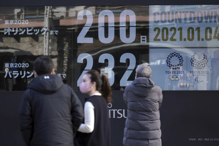 People wearing masks against the spread of the coronavirus walk in front of a countdown calendar showing 200 day to start Tokyo 2020 Olympics Monday, Jan. 4, 2021, in Tokyo. The countdown clock for the postponed Tokyo Olympics hit 200 days to go on Monday. Also on Monday, Japanese Prime Minister Yoshihide Suga said he would consider calling a state of emergency as new coronavirus cases surge to record numbers in Tokyo and neighboring prefectures. (AP Photo/Eugene Hoshiko)