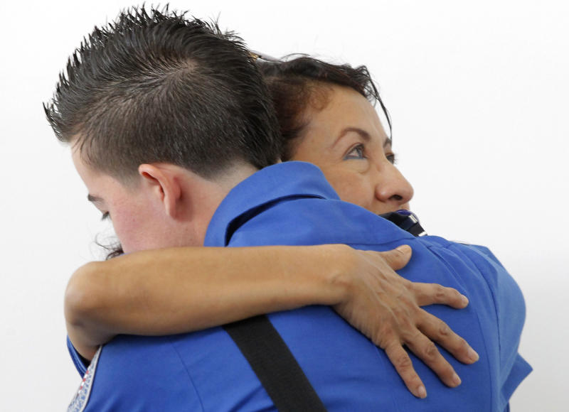 TSA officers hug each other at the Los Angeles International Airport, during a moment of silence Friday Nov. 8, 2013, to honor the Transportation Security Administration officer Gerardo Hernandez, killed by a gunman at Los Angeles International Airport a week ago. (AP Photo/Nick Ut)