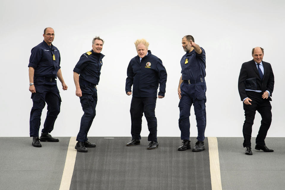 From left, Captain Angus Essenhigh, First Sea Lord Admiral Tony Radakin, Prime Minister Boris Johnson, Commodore Steve Moorhouse and Defence Secretary Ben Wallace face strong winds as they walk on the flight deck, during a visit aboard HMS Queen Elizabeth in Portsmouth, England, Friday, May 21, 2021 ahead of its first operational deployment to the Far East. (Leon Neal/Pool Photo via AP)