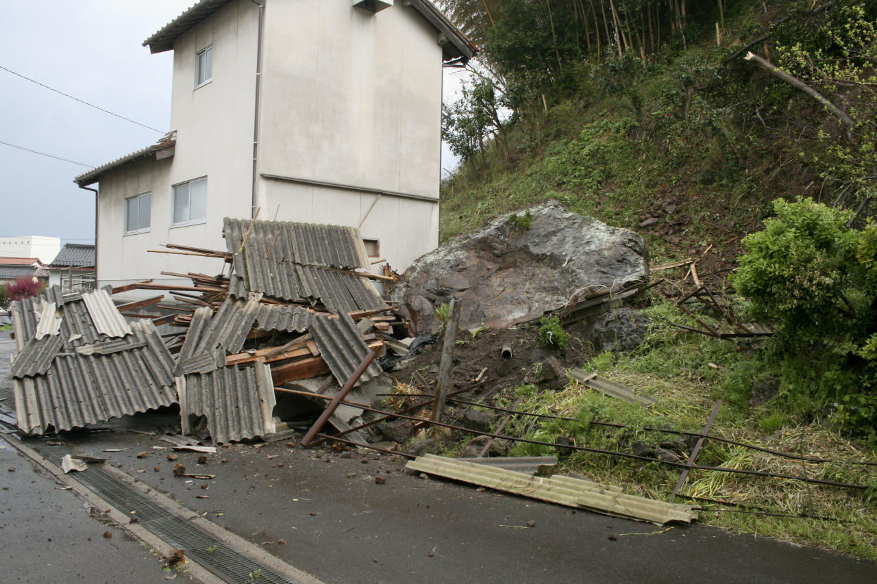 A rock sits on the ground near a house, following a landslide caused by the earthquake in Ohda, Shimane prefecture, western Japan, Monday, April 9, 2018. A strong earthquake in western Japan has cracked streets, cut water and power to a number of homes and caused slight injuries to five people. The Meteorological Agency said the magnitude 6.1 quake struck early Monday 12 kilometers (7 miles) underground near Ohda city, about 800 kilometers (480 miles) west of Tokyo. (Kyodo News via AP)