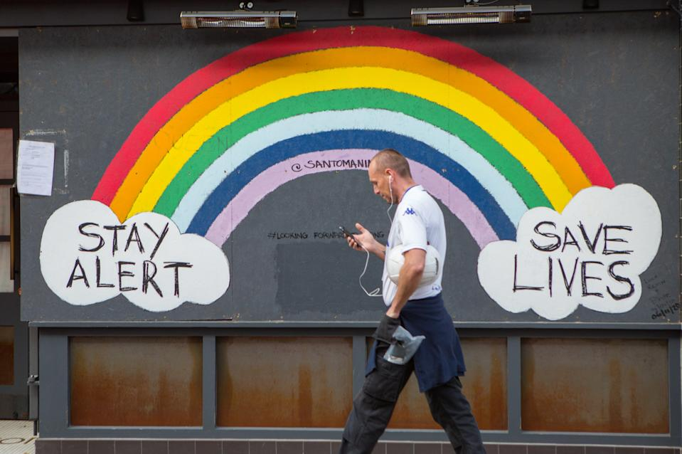 A man walks past a Stay Alert Save lives Rainbow sign in Soho, London, during the second lockdown in England in November. Photo: Pietro Recchia/SOPA Images/Sipa USA