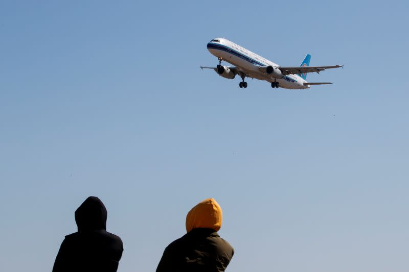 People watch a plane of China Southern Airlines land at Beijing Capital International in Beijing as the country is hit by an outbreak of the novel coronavirus